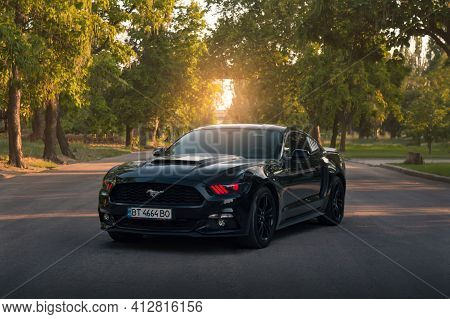 Kherson, Ukraine - July 2018. American Muscle Car Ford Mustang In A Black Color With Red Headlights.