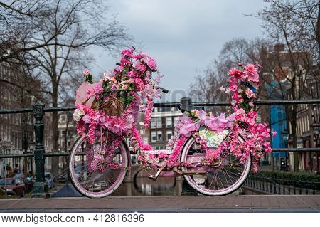 Old Vintage Bicycle Decorated With Pink Flowers On Small Bridge In Old Part Of Amsterdam