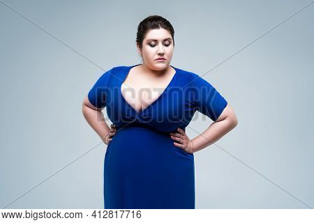 Sexy Plus Size Fashion Model In Blue Dress With Deep Neckline, Fat Woman On Gray Background, Body Po