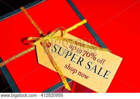 Super Sale Up To 70 Percent - Text On Gift Box Label, Red Background Top View.