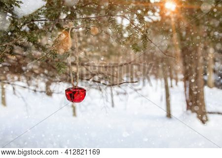 Jingle bell on tree with winter landscape in background with artificial snow