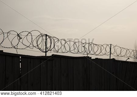 Wooden Fence With Barbed Wire Against Gray Sky