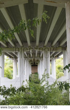 White Concrete Supports Of The Bridge In Green Plants, In Perspective. Concrete Bridge Structure