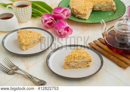Sliced Traditional Chopped Dough Napoleon Cake With Custard On A Green Plate On A Light Concrete Bac