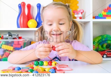 Speech Therapy, The Development Of Fine Motor Skills. Toddler Girl Is Stringing Beads On A String.