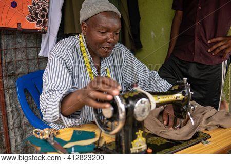 Tanzania, Masai Village - January 2020: Portrait Of Sewer Of Swiss Tailor Maasai Man Working With Se