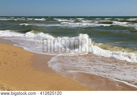 Sea Coast. Seascape With Stormy Waves, Yellow Sand Against The Sky. Waves Rolling On The Sandy Shore