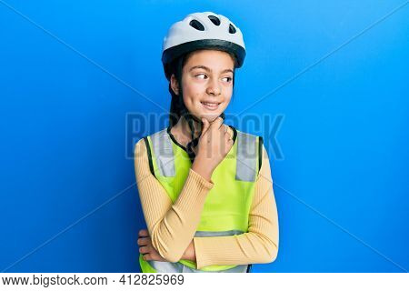 Beautiful brunette little girl wearing bike helmet and reflective vest with hand on chin thinking about question, pensive expression. smiling with thoughtful face. doubt concept.