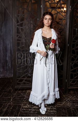 A Young Beautiful Brunette With Long Loose Hair In A White Peignoir In The Fashion Of The 19th Centu