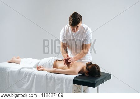 Male Masseur Tapping The Ribs Of The Palms On The Back To Young Woman In Spa Salon During Massage Pr