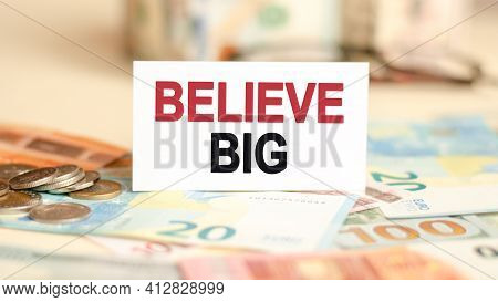 On The Table Are Bills, A Coins And A Sign On Which It Is Written Believe Big, Finance And Economics