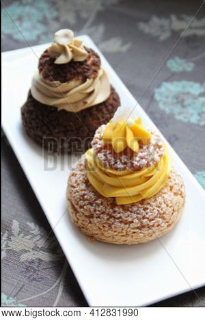 Two Puff With Cream, Dark Chocolate Puff With Cream And A Light Puff With Yellow Cream, Sweet Desser