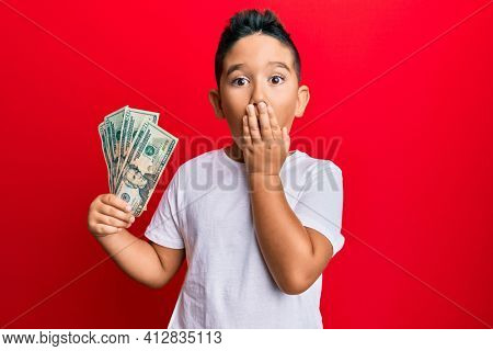 Little boy hispanic kid holding 20 dollars banknotes covering mouth with hand, shocked and afraid for mistake. surprised expression