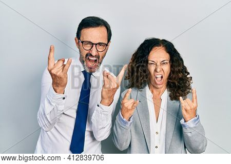 Middle age couple of hispanic woman and man wearing business office uniform shouting with crazy expression doing rock symbol with hands up. music star. heavy concept.