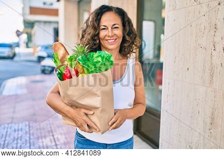 Middle age hispanic woman smiling happy holding a grocery shopping bag full of groceries at the city.