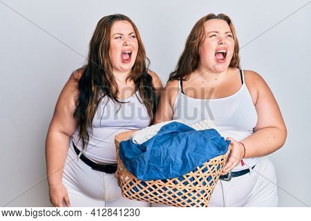 Plus size caucasian sisters woman holding laundry basket angry and mad screaming frustrated and furious, shouting with anger. rage and aggressive concept.