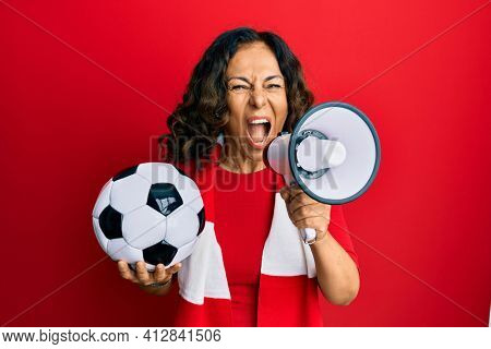 Middle age hispanic woman hooligan screaming through megaphone supporting soccer team