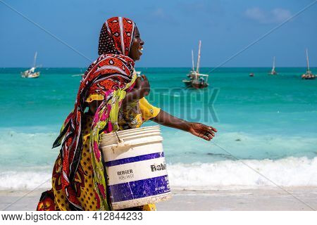 Nungwi, Zanzibar - Jan 20, 2019: Local Woman In Bright Cloth Walking By The Indian Ocean Beach With