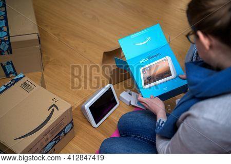 Overhead View Of Young Woman Unboxing Amazon Alexa Smart Speaker