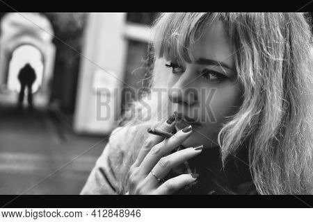 Concepts Against Violence. A Scared , Nervously Smoking Woman Stands On A Dark Street In Front Of Th