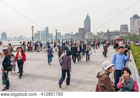 Shanghai, China - May 4, 2010: Many People Walk On Boardwalk Along River Bund Side Uner Silver Sky.