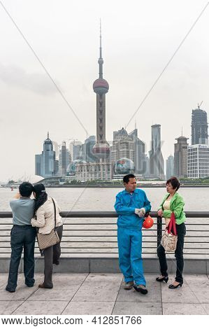Shanghai, China - May 4, 2010: Along Bund, 4 People Look Over River At Pudong Skyline With Iconic Bu