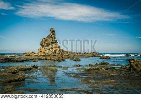 Eagles Nest Rock Formation With Reflection On Scenic Ocean Coastline
