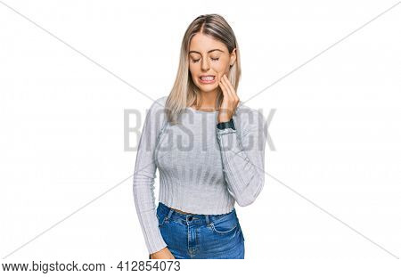 Beautiful blonde woman wearing casual clothes touching mouth with hand with painful expression because of toothache or dental illness on teeth. dentist