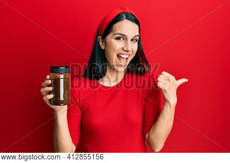 Young hispanic woman holding soluble coffee pointing thumb up to the side smiling happy with open mouth