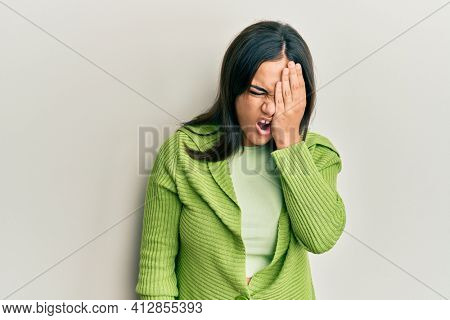 Young brunette woman wearing casual clothes yawning tired covering half face, eye and mouth with hand. face hurts in pain.