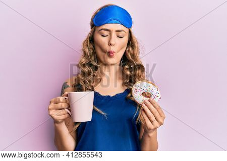 Young blonde girl wearing sleep mask and pyjama having breakfast making fish face with mouth and squinting eyes, crazy and comical.