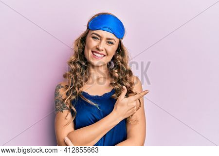 Young blonde girl wearing sleep mask and pyjama smiling cheerful pointing with hand and finger up to the side