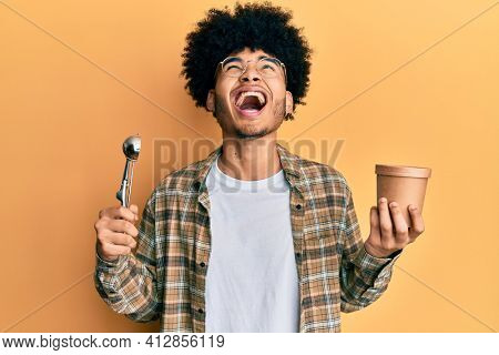 Young african american man with afro hair holding ice cream and ice cream scoop angry and mad screaming frustrated and furious, shouting with anger looking up.