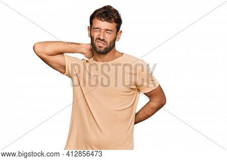 Handsome young man with beard wearing casual tshirt suffering of neck ache injury, touching neck with hand, muscular pain