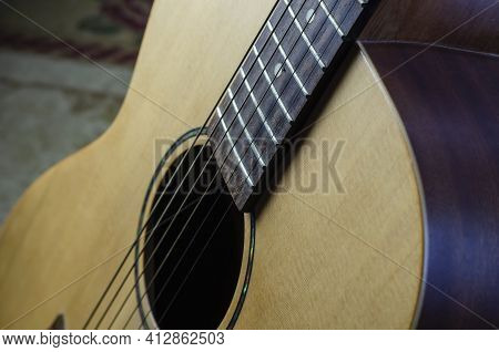 Fragment Of An Acoustic Six-string Guitar. Yellow Guitar With Strings. Indoors. Close-up. Selective