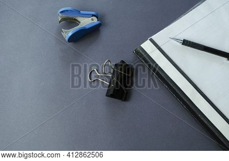 Binder Folder, Binder Clip, Staple Remover And Pencil On A Gray Table. Office Work. Office Workplace