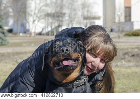 Portrait Of A Happy Woman Hugging Her Pet. An Adult Woman And A Rottweiler Are Looking At The Camera
