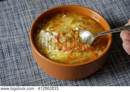 A Hand With A Metal Spoon Mixes Sour Cream In A Brown Earthenware Bowl With Cabbage Soup. A Serving