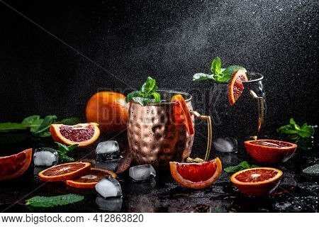 Moscow Mule Cocktail In Copper Cups With Blood Orange, Fresh Mint Leaves And Ice In Copper Mugs, Spl