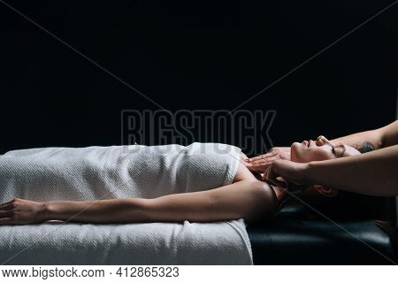Side View Of Young Relaxed Woman Lying Down On Massage Table With Closed Eyes During Shoulder And Ne