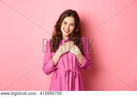 Image Of Beautiful Young Woman Holding Hands On Heart And Smiling Grateful, Express Gratitude, Sayin