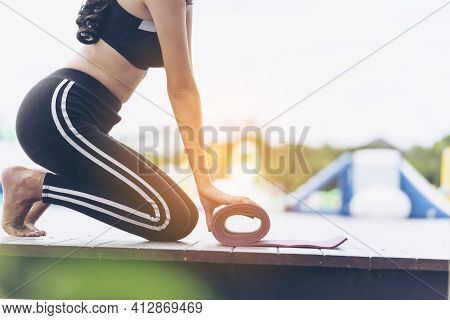 Woman Hands Rolled Up Yoga Mat Outdoor Workout. Close Up Hands Rolling Foam Yoga Gym Mat Outside Mor