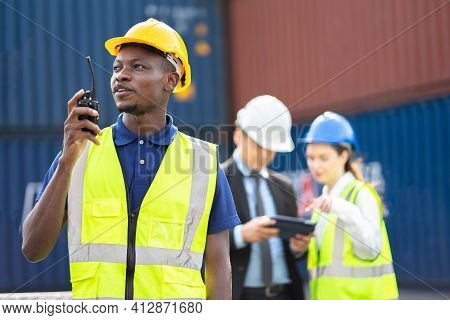 Smiling Builder Engineering In Hardhat With Walkie Talkie Over Group Of Builders At Construction Sit