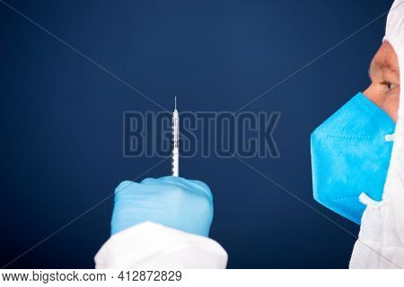 Concept of herd immunity, virus spreading in society. Doctor with syringe is preparing for vaccine.