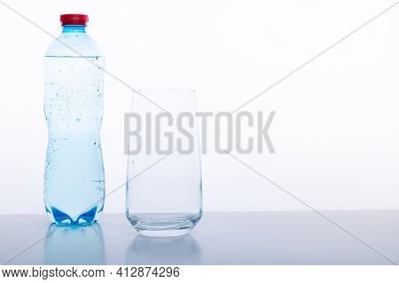 Mineral Water Bottle And Glass On A White Background. Mineral Water With Gas. Front View.