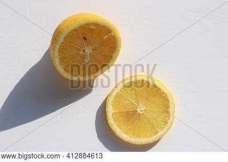 Half Of Lemon And Citrus Slice On White Table Background. Top View, Copy Space. Hard Light, Shadow.