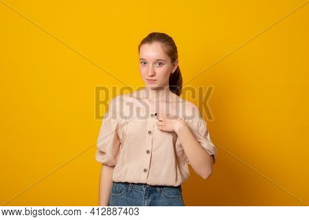 Surprised Teen Girl Points To Herself. Cute European Girl On A Yellow Background Shows A Finger At H