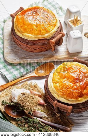 Chicken Pot Pie In The Rustic Clay Pots On A White Wooden Table, Close-up, Vertical View From Above,
