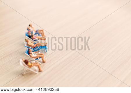 Miniature People Sunbathing On The Beach
