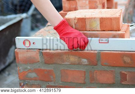 Brick Masonry: A Bricklayer Is Checking The Evenness Of A Brick Wall, Brick Foundation Using A Spiri